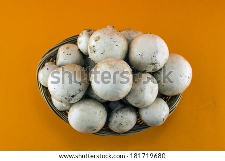 button mushrooms in straw basket, champignons. - stock photo