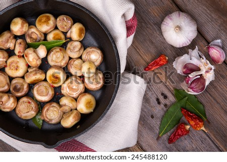 Button mushrooms with garlic, fried in a cast iron skillet, resting on a tea towel over an old wood background. - stock photo
