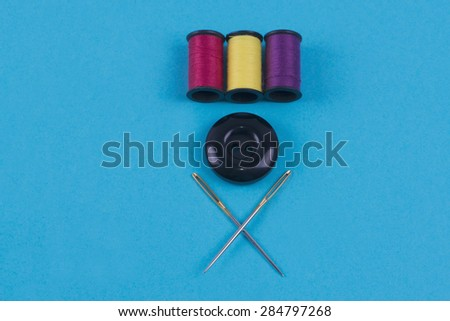 Button with needle and thread colors on a blue background - stock photo
