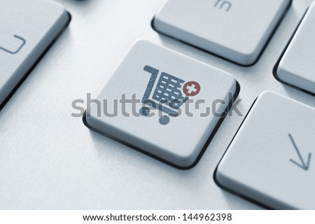 Button with shopping cart icon on a modern computer keyboard. - stock photo
