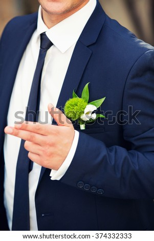 buttonhole from an carnation on the groom's suit
