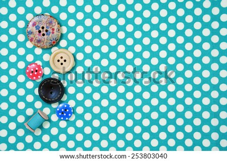Buttons on blue polka dot fabric background - stock photo