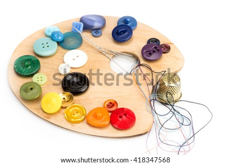 buttons, thimble, needle and thread laid on a palette on a white background - stock photo
