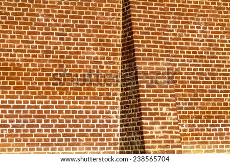Buttressed plain brick wall om a sunlit day - stock photo