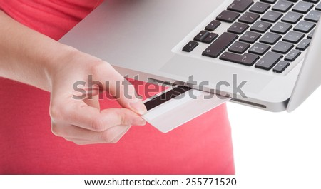 Buy and pay online using credit or debit card concept with woman holding a laptop - stock photo