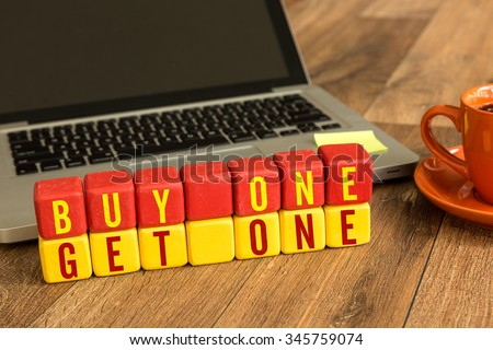 Buy One Get One written on a wooden cube in a office desk - stock photo