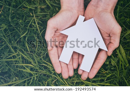 Buy or build a new house - two hands of a woman holding a white cutout house over green grass, viewed from the top. - stock photo