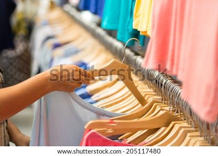 Buyer chooses a T-shirt in a boutique - stock photo