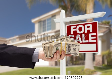 Buyer Handing Over Cash for House with Home and For Sale Real Estate Sign Behind.