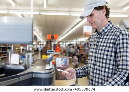 Buyer looks at the cash receipt in a supermarket