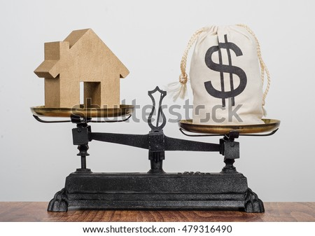 Buying a home, old antique balance scales balancing a house and a bag of money with a dollar sign on.