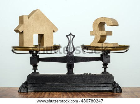 Buying a home, old antique balance scales balancing a house and a Pound sign.