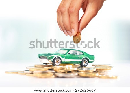 Buying car. Green car and coins over light background.