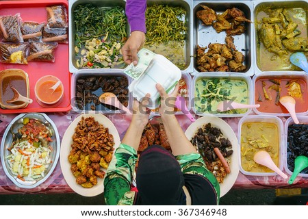 Buying food.Variety of delicious Malaysian home cooked dishes sold at street market stall in Kota Kinabalu Sabah  from top angle view. - stock photo