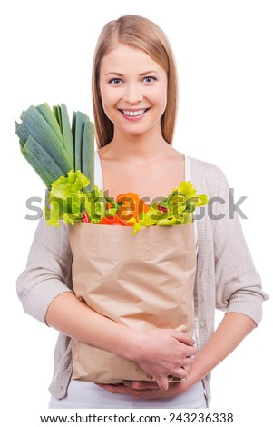 Buying for good cooking. Beautiful young woman carrying a shopping bag full of groceries and looking at camera while standing against white background