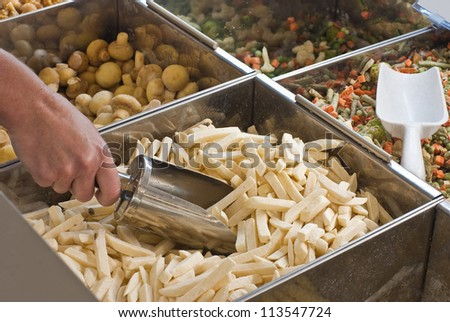 Buying frozen French fries in supermarkete - stock photo