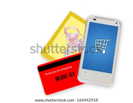 Buying online with a cell phone. Fast, easy internet shopping made with a credit card phone app. Smartphone with shopping cart icon on screen, back of red credit card, yellow gift box with ribbon.