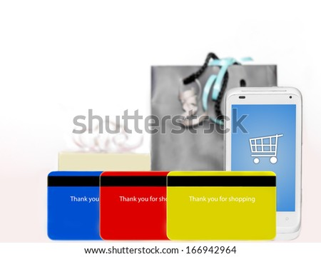 Buying online with a cellphone. Fast, easy internet shopping made with a credit card phone app. Smartphone with shopping cart icon on touch screen, 3 credit cards, gift box and bag with ribbons. - stock photo