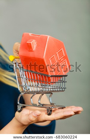 Buying property or home, real estate investment concept. Woman hand holding shopping cart with house inside