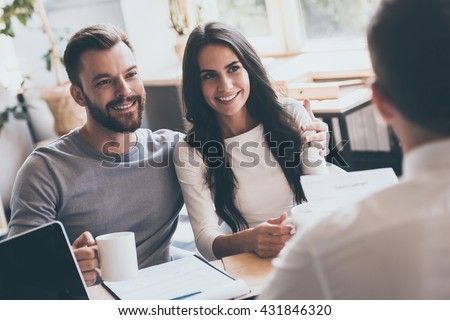 Buying something special. Young loving couple bonding to each other and looking at man sitting in front of them at the desk and holding some document - stock photo