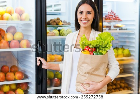 Buying the freshest products. Beautiful young woman holding shopping bag with fruits and smiling while standing in grocery store near refrigerator   - stock photo