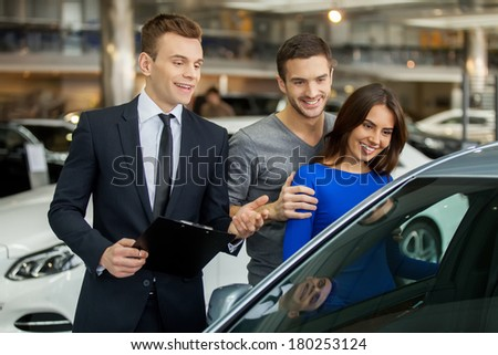 Buying their first car together. Handsome young car salesman standing at the dealership telling about the features of the car to the customers - stock photo
