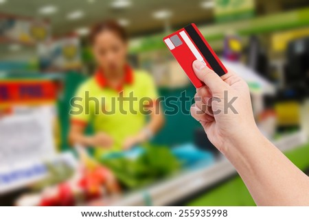 Buying with Credit Card in supermarket - stock photo