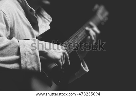 BW musician playing acoustic guitar, shallow dept of field & focus on right hand. isolated on black