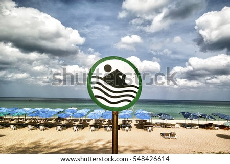 By the empty beach sand benches swimming sign umbrella blue sky clouds