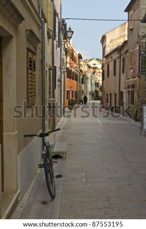 Bycicle and colourful houses with stone-paved street in Skradin - stock photo