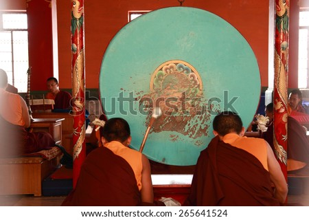 BYLAKUPPE, INDIA - MAR 27, 2015 : Buddhist monks beat drums during prayer at Namdroling Monastery on March 27, 2015 in Bylakuppe,India. Bylakuppe is second largest Tibetan refugee settlement in India. - stock photo