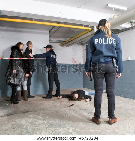Bystanders being held at a distance by a police man at a murder scene, with a police woman standing at some distance, looking at the victim - stock photo