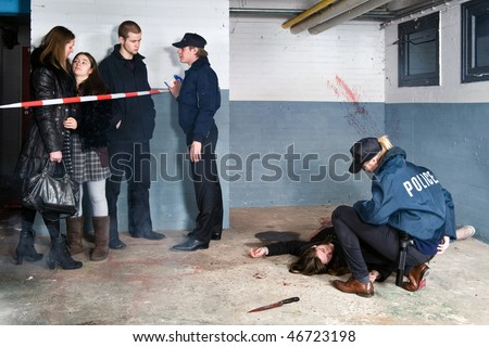 Bystanders being held at a distance by a police man at a murder scene, with a police woman tending to the victim - stock photo