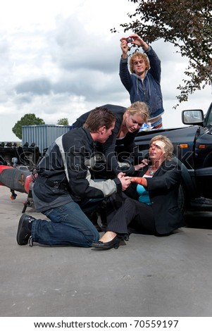 Bystanders checking up and providing first aid to an injured bleeding driver after a car crash. A man is taking pictures as amateur journalist for social media networks - stock photo