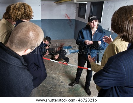 Bystanders looking at a crime scene with a murdered woman, whilst a police officer is taking testemonies from witnesses in the crowd - stock photo