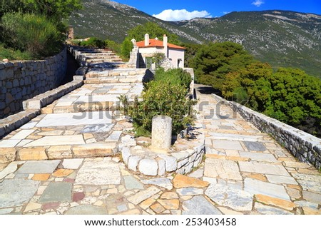 Byzantine monastery with sunny access road surrounded by green forest, Greece - stock photo