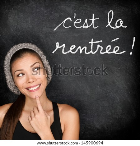 C'est la Rentrée Scolaire - French college university student woman thinking Back to School written in French on blackboard by female on chalkboard. French language at college or high school. - stock photo