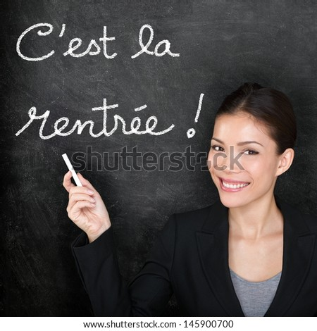 C'est la Rentrée Scolaire - French teacher woman. Back to School written in French on blackboard. Female professor teaching French language at university, high school or primary school. - stock photo