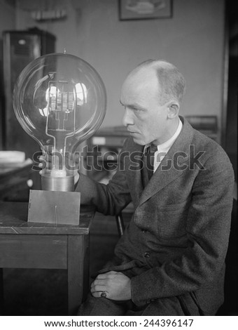 C.W. Mitman, Head Curator, Department of Engineering and Industries of the Smithsonian Institute, holds a giant light bulb. For contrast a midget bulb is placed beside it. March 1923.