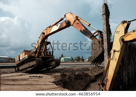 CA MAU, VIET NAM- JULY 16,2016: Vietnamese excavator driver control vehicle to build breakwater at beach to protect seaside from erosion at Camau, Vietnam