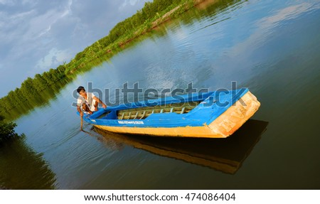 CA MAU, VIET NAM- JULY 16, 2016: Vietnamese man catch fish on river, people and row boat reflect on water, beautiful green tree from mangrove forest make wonderful scene in evening at Mekong Delta