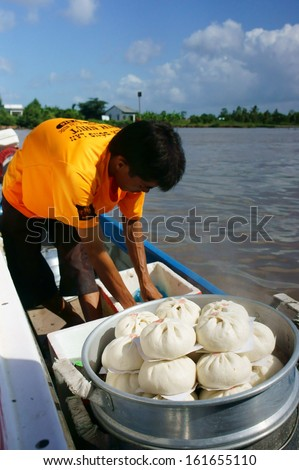 CA MAU, VIET NAM- JUNE 29: Amazing view with food vendor, he drive the motor boat and sell dumpling on riverr, this is special culture of Mekong delta, Ca Mau, Vietnam, June 29, 2013