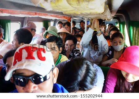 CA MAU, VIET NAM- JUNE 29, 2013. People sit in overcrowded, packed like sardines with number of passenger over assign, they look unhappy on non-stop express passenger boat. June 29, 2013