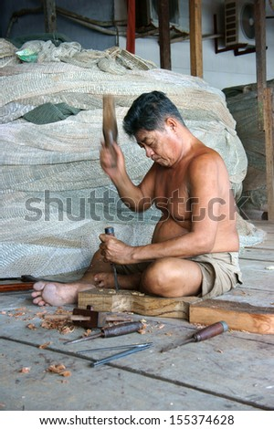 CA MAU. VIET NAM- JUNE 29. Portrait of the man with carpentry tool bore a hole in section of a tree trunk, there are some fishing net roll to fisherman catch fish. In vertical frame. June 29, 2013