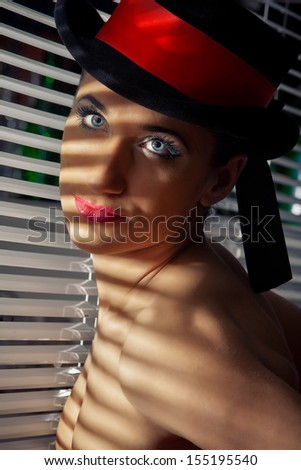 Cabaret performer in black top hat looking through a jalousie  - stock photo