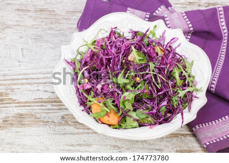 Cabbage salad. Red cabbage salad filled with nuts, broccoli , apples and fresh herbs. Macro, selective focus - stock photo