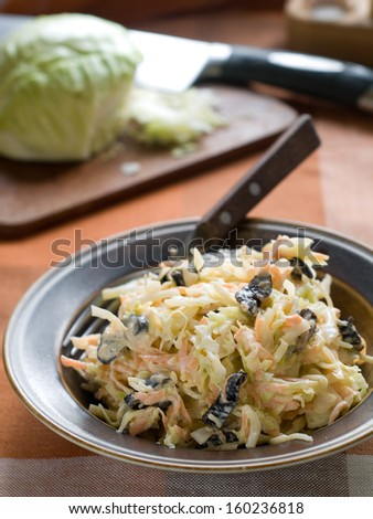 Cabbage salad with carrot and prunes, selective focus