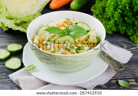 Cabbage salad with cucumber. Salad and vegetables on wooden table - stock photo