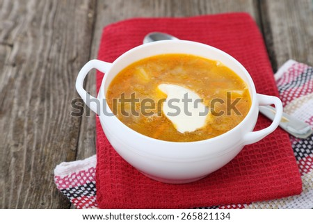 Cabbage soup in a white plate on old wooden table . - stock photo