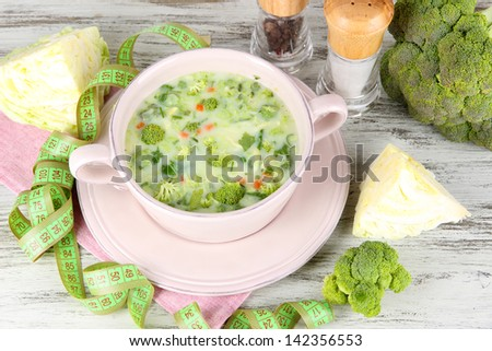 Cabbage soup in plate on napkin on wooden table